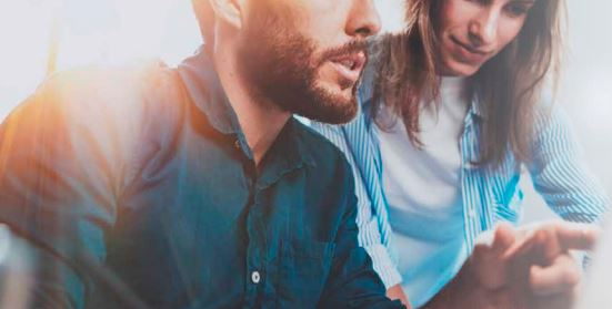 ein junger Mann und eine junge Frau schauen gemeinsam auf einen Bildschirm, er zeigt auf etwas am Bildschirm