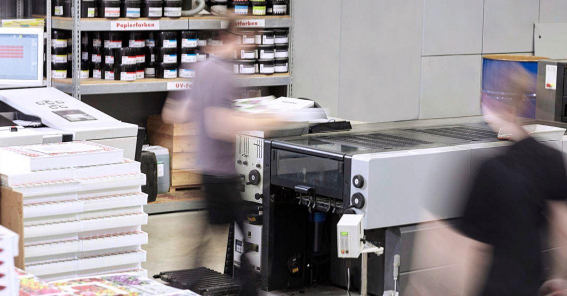 Mitarbeiterin und Mitarbeiter in einer Produktion an einer großen Druckereimaschine