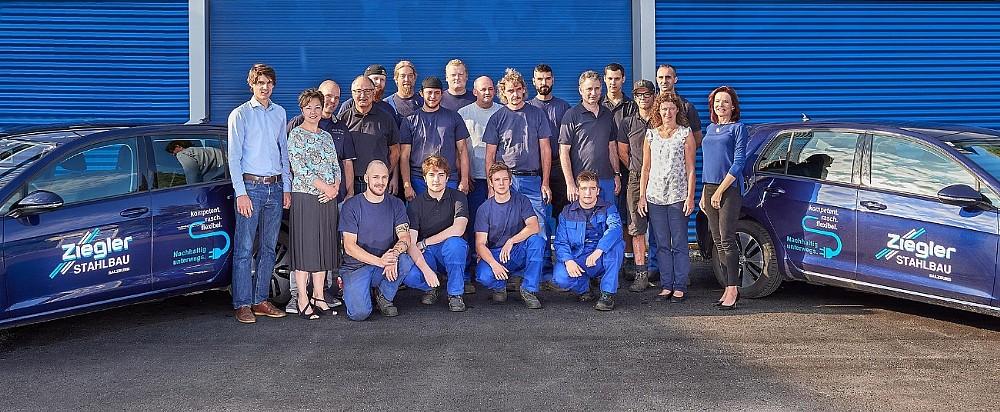 Foto vom gesamten Team der Firma Ziegler Stahlbau in Salzburg 23 Personen und 2 Firmenautos
